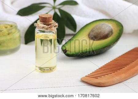 Avocado oil in bottle, green fruit, comb. Cosmetic benefits, healthy hair and skin care.
