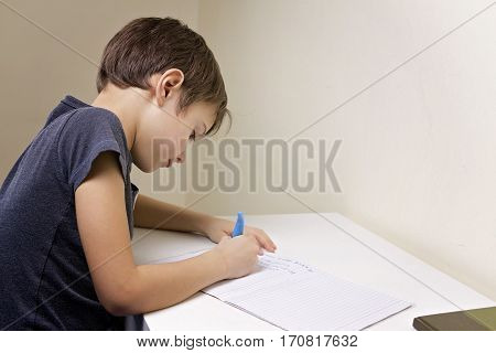 Boy writing at the desk at home. Child doing his homework. School, children, education concept