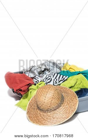 Studio shot of a suitcase with scattered clothing straw hat lying in front of the suitcase. Everything is on a white background. Vertically.