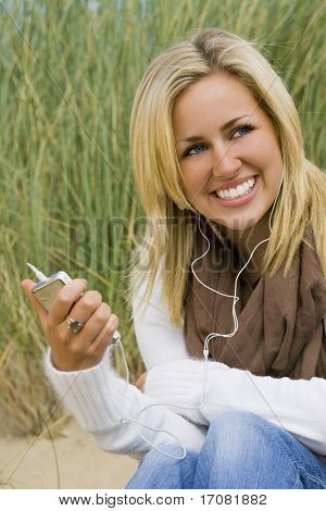 A naturally beautiful young blond woman listening to music on a beach backed with long green grass