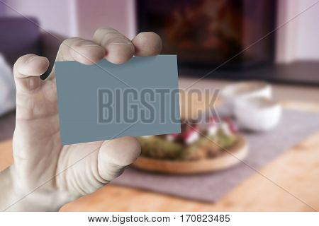 closeup of mans hand holding an empty business card in front of stylish living room