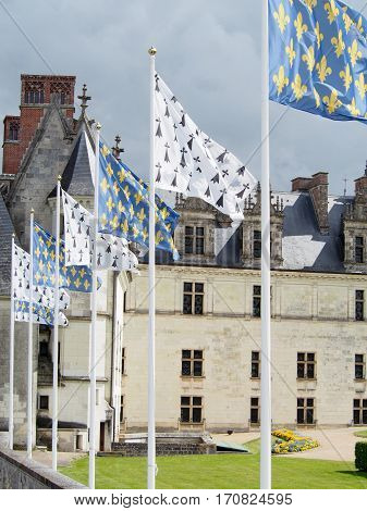 Flags sporting the fleur-de-lis fly in a row in front of the Amboise Chateau in the Loire Valley of France.