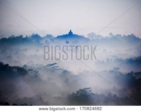 The sun rises on a foggy morning over Borobudur temple near Yogyakarta Indonesia.