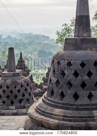 Bell-shaped stupas decorate the Borobudur temple near Yogyakarta Indonesia.