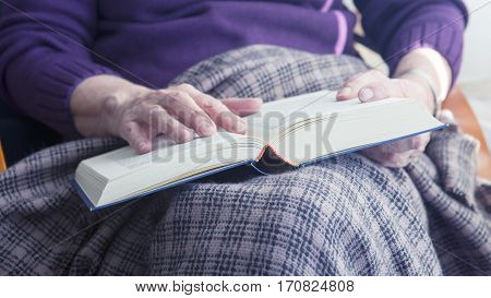 closeup of older woman sitting by window with blanket and reading a book