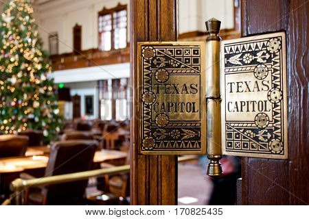 A detail of a door hinge in the Texas State Capitol building with a Christmas tree lit up in the background.