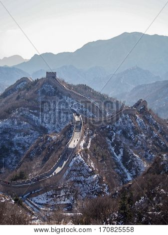 The Great Wall of China sprawls across the Chinese landscape on a cold winter day.