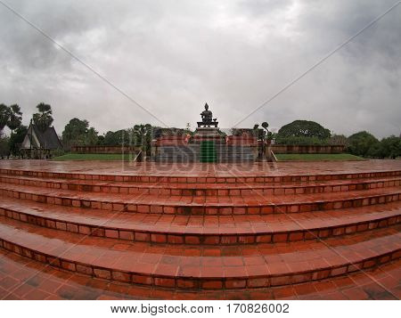 Red brick platform with statue of King Ramkhamhaeng at Sukhothai Historic Park Thailand.