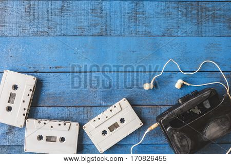 Top view of Cassette player with audio tape on blue wooden table background Free space for text