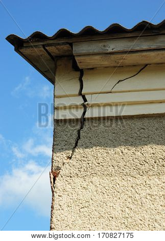 Damaged house stucco wall corner. Cracked Wall near Roof Construction.