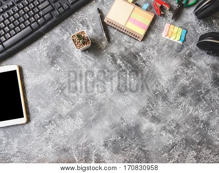 Top view of Keybroad with tablet, headphone, notebook, cactus and Office supplies on Grunge gray background Free space for text