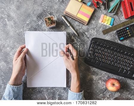 Top view of Male hands holding paper sheet with Office supplies on Grunge gray background