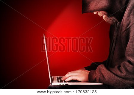 Male computer hacker wearing a hooded top leaning over a laptop with red warning background. The screen light illuminates the man with a beard performing illegal activities. Graduated copy space on the left