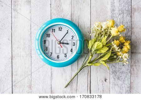 Top view of Clock with beautiful flowers on wooden table background