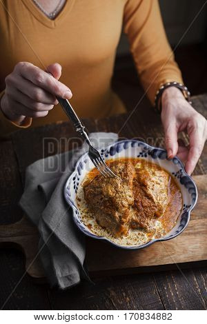 Woman eating from a bowl of chicken Butter at the table vertical