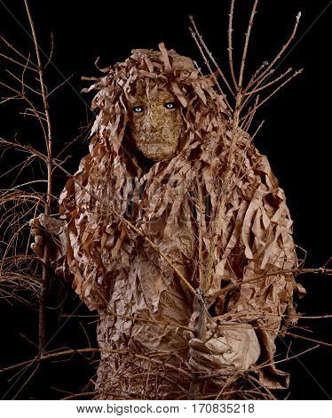 Man in a wood goblin costume holding a withered trees. Environmental protection