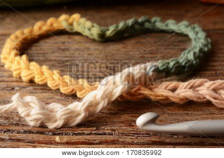 A low angle image of crochet yarn and a single crochet hook.