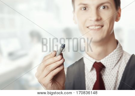 Smiling businessman holding a pen at his office