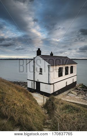 Landscape Image Of Derelict Abandoned Fishing House On England Solent Coast During Moody Sunset
