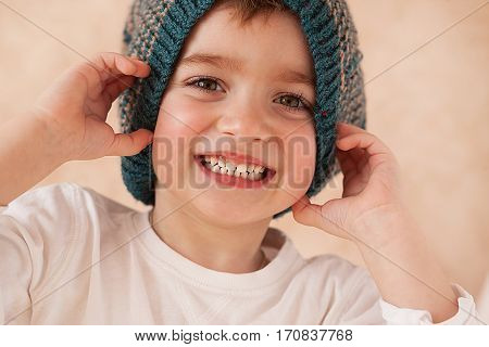 face close-up beautiful boy in a knitted hat baby smile