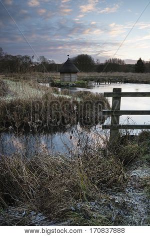 Beautiful Landscape On Frosty Winter Morning Of Eel Traps Over Flowing River In English Countryside