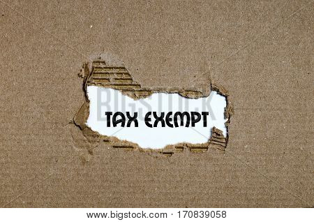 The Word Tax Exempt Appearing Behind Torn Paper