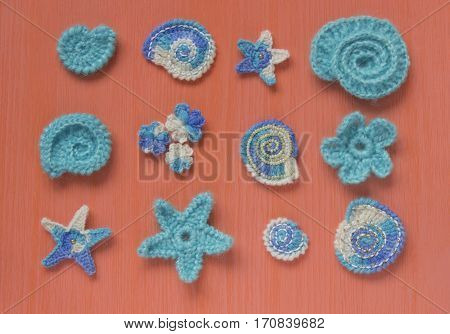 Marine background with cotton lace crochet craft elements: stars shells flowers made of soft acrylic wool yarn. Crocheted creative doilies. Decorative needlework marine design. Selective soft focus