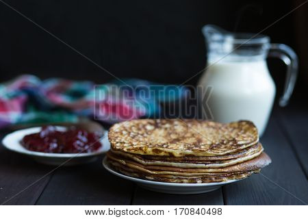 Homemade pancakes with raspberry jam on a dark wooden table. Top view with hands. Shrove Tuesday.
