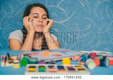 Attractive woman searching for muse while looking on paints
