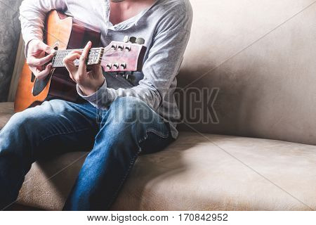 Casual Young Man Playing Guitar On Sofa At Home.