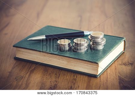 Business Concept. Closeup Stack Of Coins, Pen And Old Book On Table.