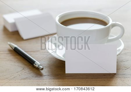 Blank Business Cards, Pen And Cup Of Coffee On Wooden Table.
