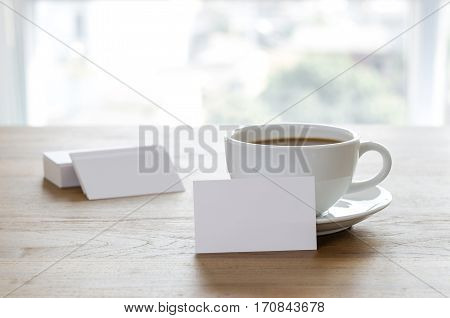 Blank Business Cards And Cup Of Coffee On Wooden Table.