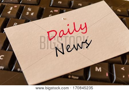 Daily news text concept on white memo and dark keyboard background