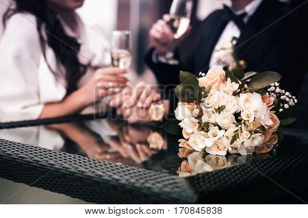 Newlyweds sitting at mirrored table and drinking champagne. In the foreground is pink bouquet