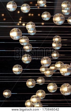 lighting balls on the chandelier in the lamplight light bulbs hanging from the ceiling lamps on the dark background selective focus horizontal