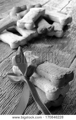 A close up image of several large bone shaped dog treats on a wooden table.