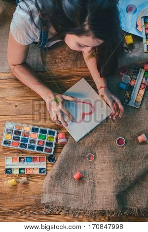 Young female artist painting picture in studio on the floor
