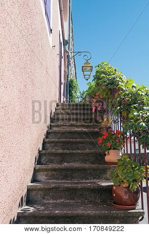 Old staircase in front of the door decorated with plants in flower pots in the picturesque village of Mirabel Ardèche, France.