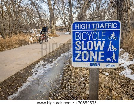FORT COLLINS,  CO, USA - JANUARY 2, 2017: Bicycle slow zone sign on the Poudre River trail, a popular trail for biking, running and dog walking even in winter conditions.