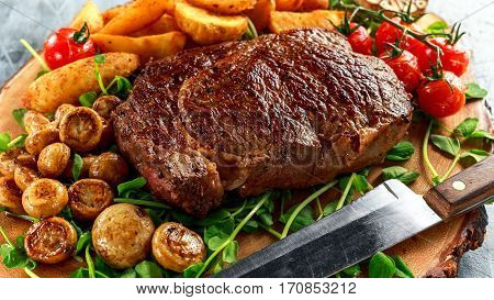 Cooked Beef Ribeye Steak with Potato, Mushrooms, tomatoes on wooden board