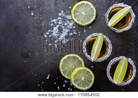 Alcohol, junk food, party, holidays concept. Golden mexican tequila shot on a grunge black table with salt and lime. Copy space background, top view flat lay overhead