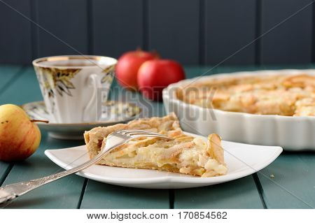 Apple tart with cup of tea and three whole apples horizontal