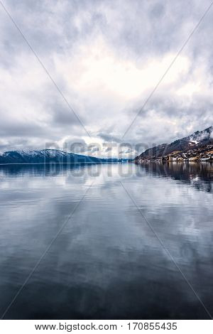 Norwegian fjord landscape with mountains under a overcast sky