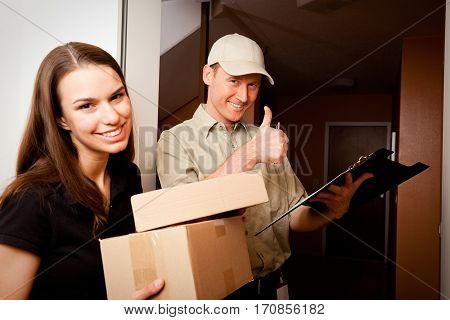 a delivery boy is hading over two packets to a young female customer and giving us a thumbs up because he loves his job so much focus is on the delivery boy.