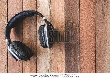 Top view of Headphones on wooden table background. Free space for text