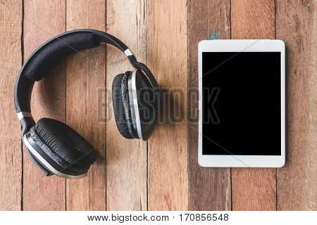 Top view of Headphones with Tablet on wooden table background
