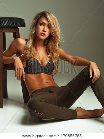 Suntanned girl in a bra-top and pants sits on the floor. She leaned against stool.