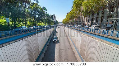 Streets scenes of Madrid.  Parking at the side of Calle del Alfonso where it enters a tunnel that runs under an intersection, above.  Car travels down Alfonso XII Street toward tunnel entrance.