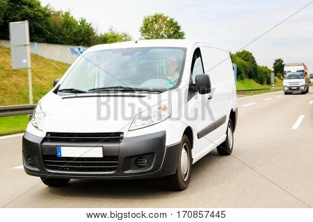 a white delivery van on a highway, motion blur. driver is model-released.
